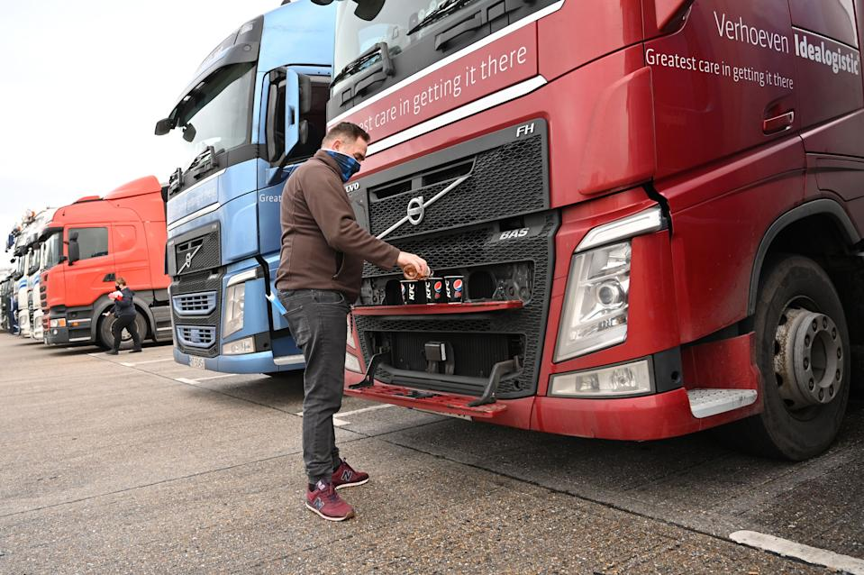 A Polish driver pours drinks for him and his colleagues as they wait at a truck stop off the M20 leading to Dover near Folkestone in Kent, south east England on December 22, 2020, after France closed its borders to accompanied freight arriving from the UK due to the rapid spread of a new coronavirus strain. - Britain sought to sound a note of calm saying they were working as fast as possible to unblock trade across the Channel after France shut its borders to UK hauliers in a bid to contain a new variant of the coronavirus. (Photo by JUSTIN TALLIS / AFP) (Photo by JUSTIN TALLIS/AFP via Getty Images)