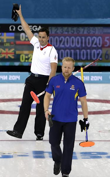 Britain's skip David Murdoch, left, celebrates while Sweden's skip Niklas Edin, walks off the ice sheet after being beaten by Murdoch's team during the men's curling semifinal game at the 2014 Winter Olympics, Wednesday, Feb. 19, 2014, in Sochi, Russia. (AP Photo/Wong Maye-E)