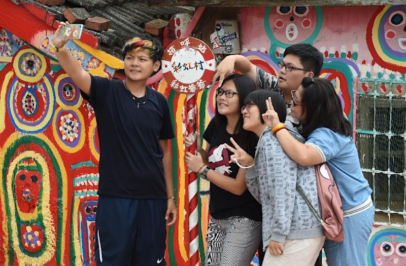 Tourists pose for selfies next to artwork by artist Huang Yung-fu, while visiting the Rainbow Village in Taichung, central Taiwan (AFP Photo/Sam Yeh)
