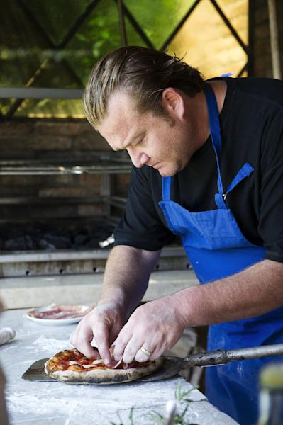 """This book cover image released by Ballantine Books shows Michael White preparing a pizza, a dish from his book """"Classico E Moderno: Essential Italian Cooking,"""" with Andrew Friedman. White is the chef and owner of Marea restaurant in New York. (AP Photo/Ballantine Books, Evan Sung)"""