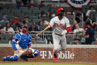 Philadelphia Phillies' Didi Gregorius (18) follows through on three-run home run as Atlanta Braves catcher Travis d'Arnaud (16) looks on in the fourth inning of a baseball game Sunday, April 11, 2021, in Atlanta. (AP Photo/John Bazemore)