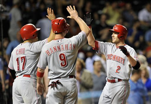 Cincinnati Reds' Shin-Soo Choo (17), Jack Hannahan (9) high five Zack Cozart after his three-run home run against the Chicago Cubs during the eighth inning of a baseball game Tuesday, June 11, 2013, in Chicago. (AP Photo/Jim Prisching)