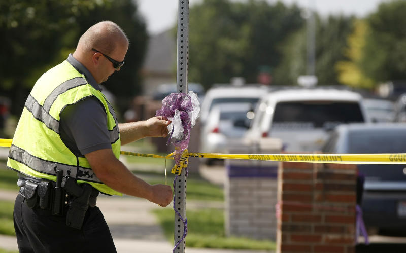 An officer tapes off the scene of an officer involved shooting Tuesday, July 23, 2013, in Saginaw, Texas. The officer was shot as he served a search warrant in an investigation into the killing of a 6-year-old girl whose naked, bound body was found wrapped in a tarp on the corner of a North Texas residential street, police said. Saginaw police spokesman Damon Ing said a person at the house where officers were serving the warrant was also shot. (AP Photo/The Fort Worth Star-Telegram, Khampha Bouaphanh) MAGS OUT; (FORT WORTH WEEKLY, 360 WEST)