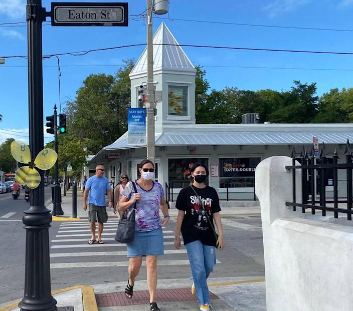 Passersby on Duval Street in Key West wear masks on Nov. 3, 2020. The city of Key West is considering a curfew to help stop the spread of the novel coronavirus.