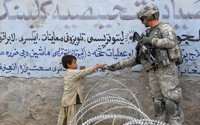 A US soldier from 4th Infantry Division 4 Brigade Alpha Company presents a gift to an Afghan child during a patrol at Khogiani in Langarhar  - KIM JAE-HWAN /AFP