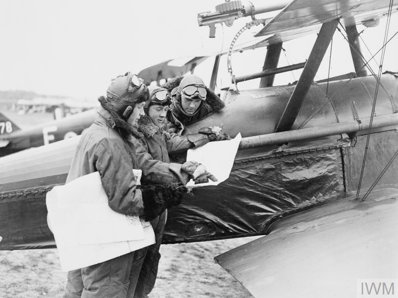 """<p>In 1926 Leslie Irvin, in United Kingdom, set up a manufacturing unit, which was supplying flying jackets made out of sheepskin. This unit was the main supplier of flying jackets to Royal Air Force during most of World War II. (Image: <a rel=""""nofollow"""" href=""""https://commons.wikimedia.org/wiki/File:Three_pilots_of_No._1_Squadron,_RFC,_studying_maps_by_an_S.E.5a_at_Clairmarais_aerodrome.jpg"""">Wikimedia Commons</a>) </p>"""