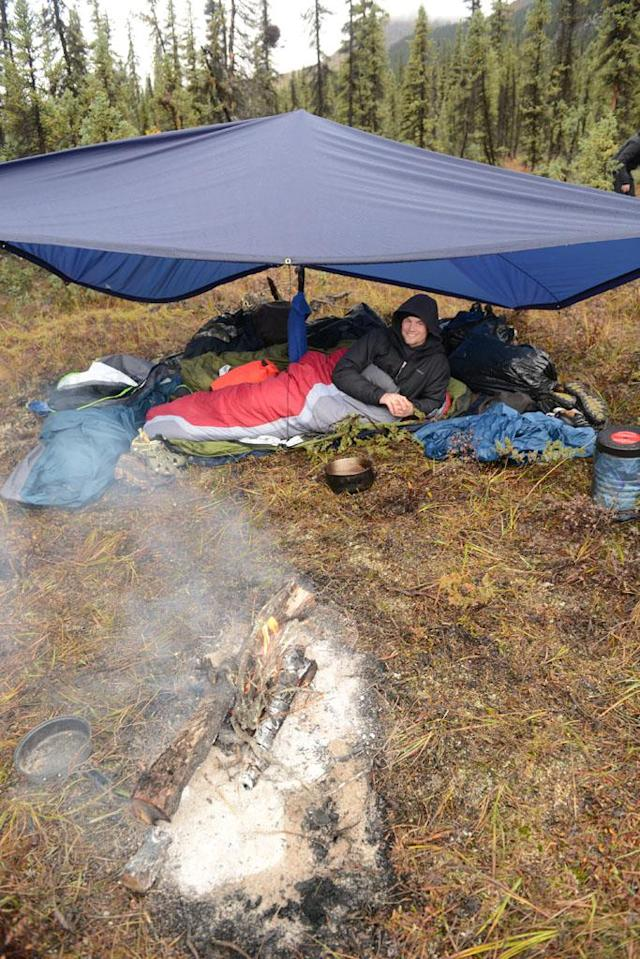 Arrigetch Peaks, Alaska, USA: Dallas Seavey laying underneath tent at a campsite.