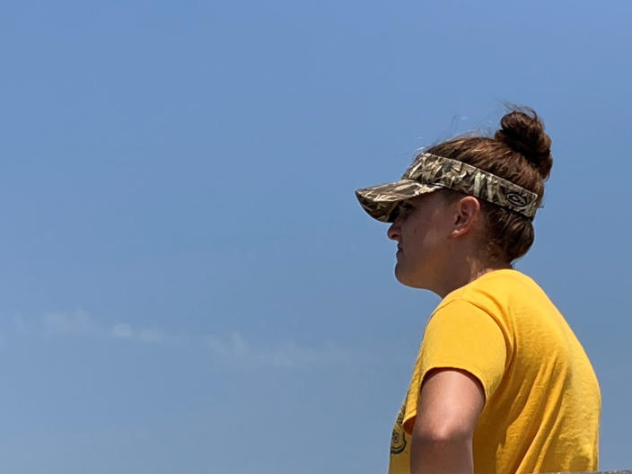 Chelsea Coleman, a volunteer who came out to help look for the seven missing people who were aboard the Seacor Power when it capsized on April 13, scans the horizon on Thursday, April 30, 2021, along the Louisiana coast. Volunteers have been searching by air and boat for any sign of those still missing. (AP Photo/Rebecca Santana)
