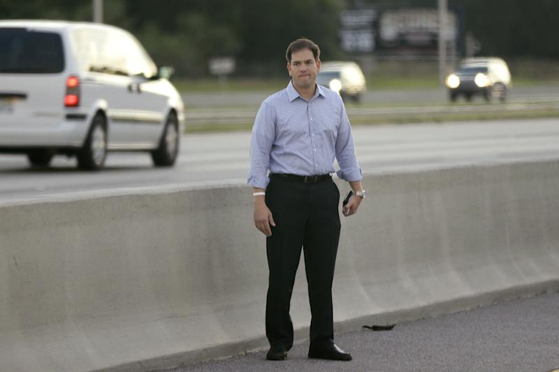 Sen. Marco Rubio, R-Fla., who is traveling with Republican presidential candidate and former Massachusetts Gov. Mitt Romney, stands alongside Interstate 4 in Lakewood Crest, Fla., Saturday, Oct. 27, 2012 after the motorcade was stopped. The 12-year-old daughter of Sen. Rubio had been airlifted to a hospital after a Saturday motor vehicle accident. A Rubio spokesman reports that the girl is in stable condition. (AP Photo/Charles Dharapak)