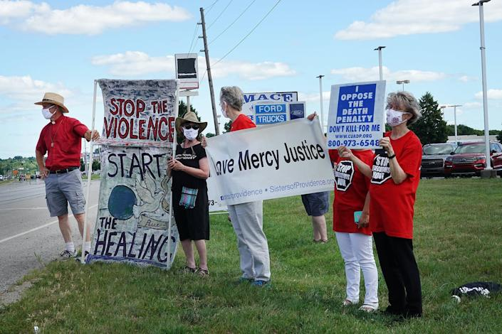 Half a dozen people hold anti-death penalty signs on a highway.