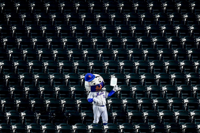 "Mr. Met stands amongst empty seats with a sign reading ""I found Nimmo"" as Brandon Nimmo (not pictured) bats."