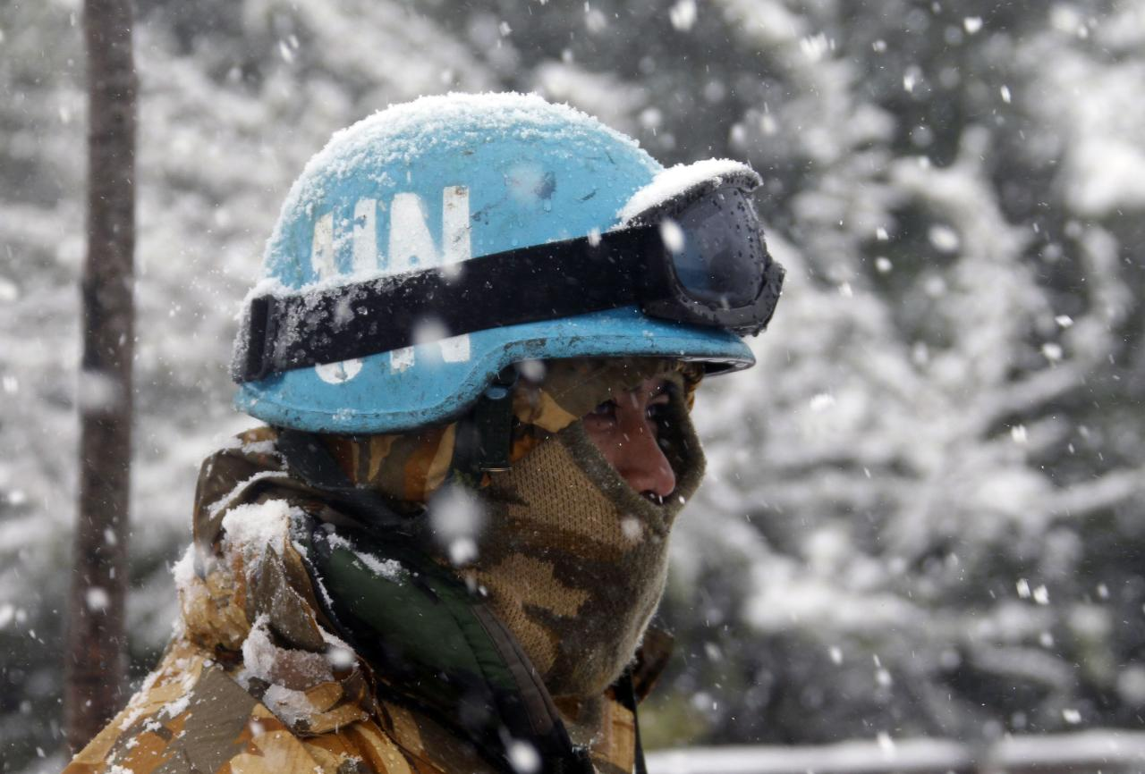 An Indonesian soldier from the United Nations Interim Forces in Lebanon (UNIFIL) is seen during a snow fall in the southern Lebanese village of Adaisseh December 13, 2013. A powerful winter storm sweeping the eastern Mediterranean this week is causing mayhem across the region. The storm, named Alexa, is expected to last until Saturday, bringing more snow, rain and freezing temperatures to large swathes of Turkey, Syria, Lebanon, Jordan, Israel and the Palestinian territories. REUTERS/Ali Hashisho (LEBANON - Tags: ENVIRONMENT)