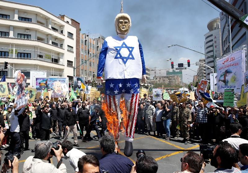 Iranian protestors burn an effigy of US President Donald Trump dressed in an Israeli flag during a rally to mark Qods Day in Tehran on June 8, 2018