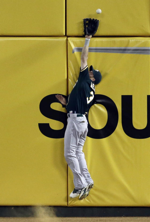 Oakland Athletics left fielder Craig Gentry is unable to reach a run-scoring double by Texas Rangers' Alex Rios in the fourth inning of a baseball game, Tuesday, April 29, 2014, in Arlington, Texas. The hit scored Adrian Beltre. (AP Photo/Tony Gutierrez)