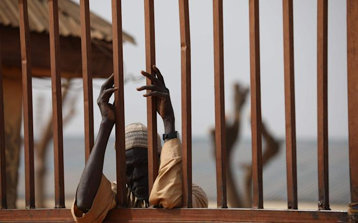 A parent waits outside the Government Science Secondary school in Kankara