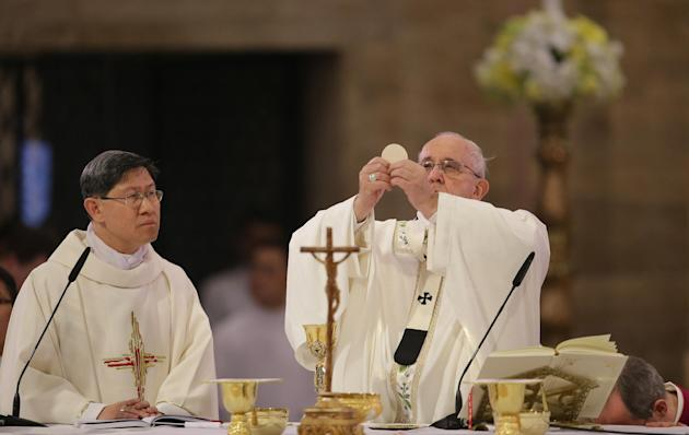 Pope Francis, right, lifts the host beside Cardinal Luis Antonio Tagle, archbishop of Manila, as he officiates a mass with clergy and religious at the Cathedral Basilica of the Immaculate Conception in Manila, Philippines, Friday, Jan. 16, 2015. (AP Photo/Aaron Favila)