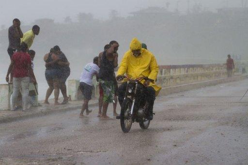 Local residents stay under the rain in Enriquillo, southwestern Dominican Republic, as Tropical Storm Isaac roared toward the island of Hispaniola