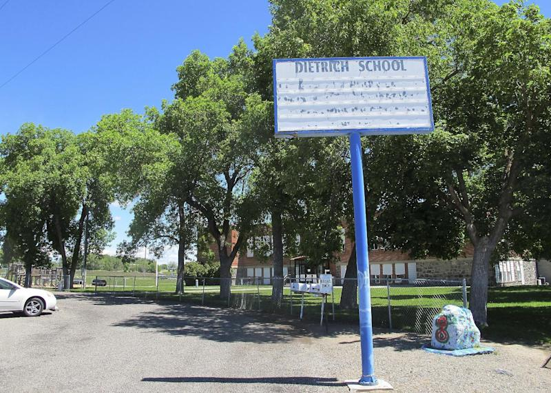 FILE - In this May 26, 2016, file photo, an empty school reader board stands in front of the only school building in Dietrich, Idaho. The small community is struggling with the national attention brought by reports that a disabled black football player was raped by his white high school teammates. The allegations of racist taunts and physical abuse suffered by the teen were revealed this month when the family filed a $10 million lawsuit against the Dietrich School District. (AP Photo/Kimberlee Kruesi, File)