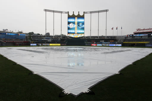 A tarp covers the infield as the rain falls at Kauffman Stadium after the game was called between the Kansas City Royals and the New York Yankees in Kansas City, Mo., Sunday, June 9, 2014. (AP Photo/Colin E. Braley)