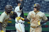 San Diego Padres' Manny Machado, right, is greeted by Jurickson Profar, left, after they both scored on a single by Wil Myers off Pittsburgh Pirates starting pitcher Luis Oviedo during the seventh inning of a baseball game in Pittsburgh, Monday, April 12, 2021. (AP Photo/Gene J. Puskar)
