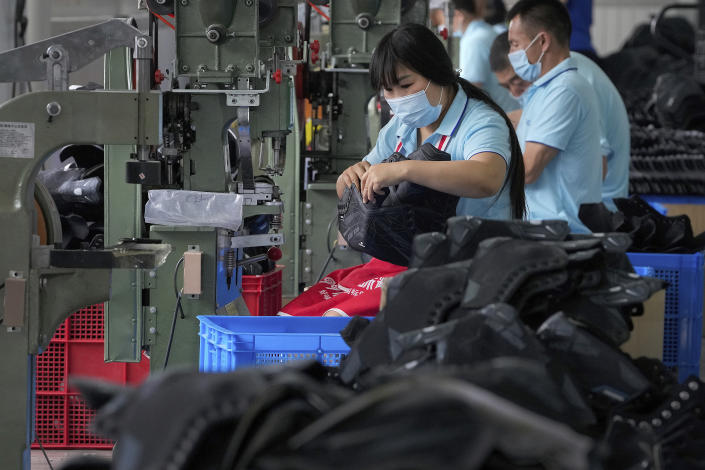 FILE - In this July 15, 2021, file photo, workers assembly ice-skating shoes at a manufacturing factory in the ice and snow sports equipment industry park in Zhangjiakou in northwestern China's Hebei province. China's manufacturing growth in July slowed to its lowest level in 15 months as export demand weakened and factories coped with disruptions in supplies of raw materials and components, two surveys found. (AP Photo/Andy Wong, File)