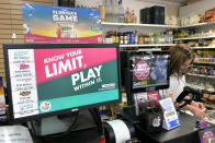 A clerk takes an order for lottery tickets next to a sign reminding customers to play responsibly, Wednesday, Jan. 13, 2021, in Orlando, Fla. Lottery players will have a shot Friday night at the fifth-largest jackpot in U.S. history after no tickets matched all the numbers in the latest Mega Millions drawing. (AP Photo/John Raoux)