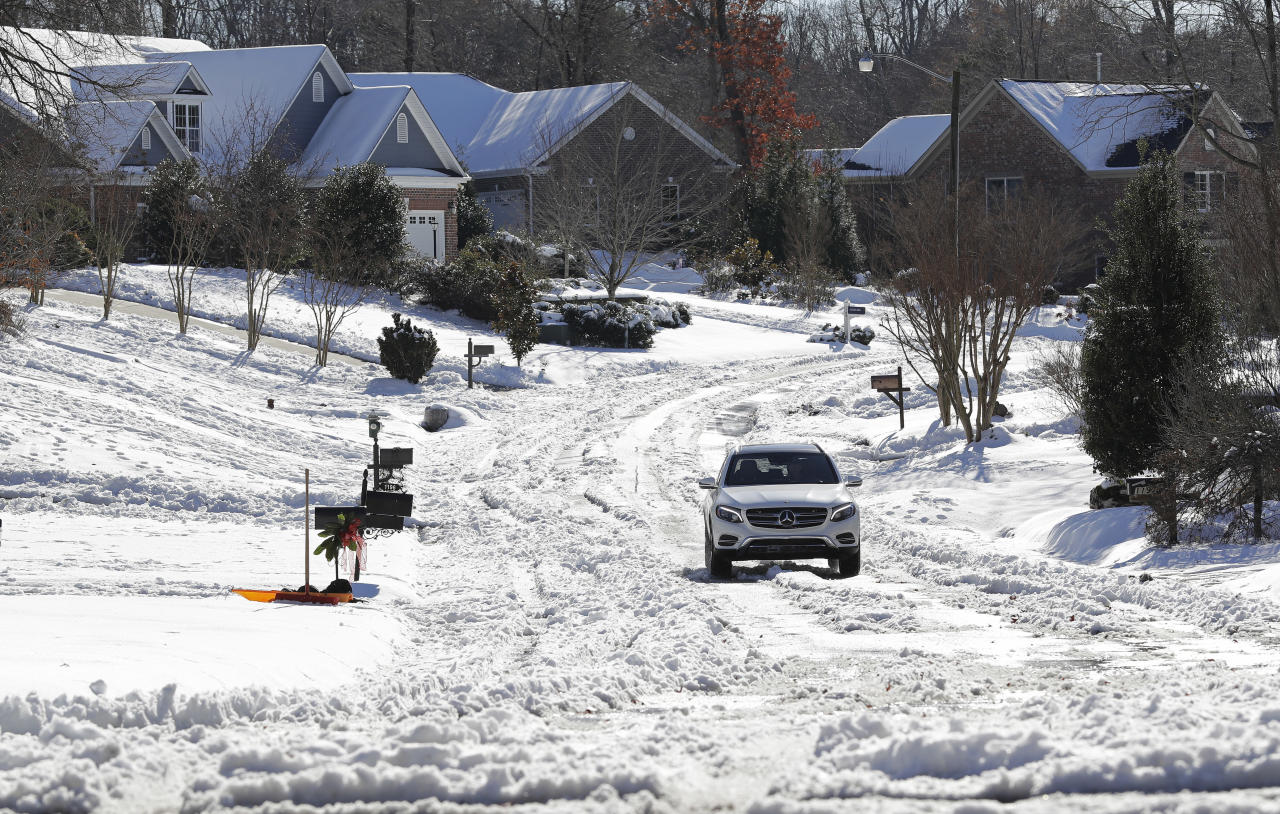 A car travels down a snow covered street in a neighborhood in Greensboro, N.C., Tuesday, Dec. 11, 2018. Several Southern states hit hard by a wintry storm were gradually warming Tuesday, but forecasters warned that temperatures in many areas will plunge below freezing again Tuesday night. That will refreeze the melting snow, making some roads treacherous. (AP Photo/Chuck Burton)