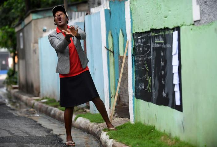 Educator Mckoy Phipps teaches a lesson with a blackboard painted on a wall during the coronavirus disease (COVID-19) outbreak in Kingston