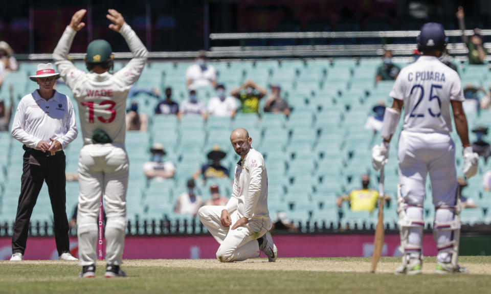 Australia's Nathan Lyon reacts after an appeal for LBW against India's Cheteshwar Pujara, right, is rejected during play on the final day of the third cricket test between India and Australia at the Sydney Cricket Ground, Sydney, Australia, Monday, Jan. 11, 2021. (AP Photo/Rick Rycroft)