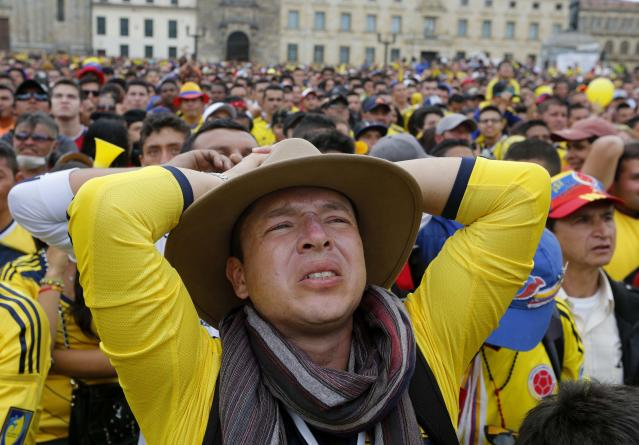 Colombia fans react after Brazil scored a goal during their 2014 World Cup quarter-finals soccer match against Colombia at a screening in Bolivar Square, Bogota July 4, 2014. REUTERS/John Vizcaino (COLOMBIA - Tags: SPORT SOCCER WORLD CUP)