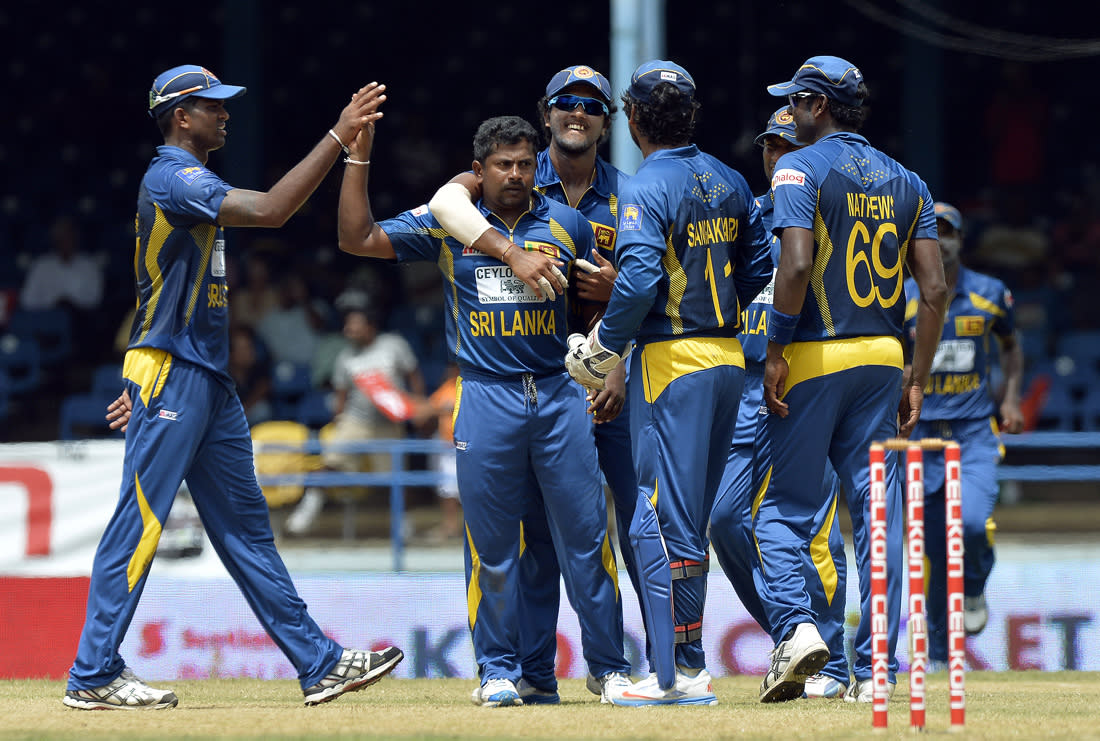 Sri Lankan cricketer Rangana Herath (C) celebrates with teammates after dismissing Indian cricket team captain Virat Kohli during the sixth match of the Tri-Nation series between India and Sri Lanka at the Queen's Park Oval stadium in Port of Spain on July 9, 2013. Sri Lanka won the toss and elected to field first. AFP PHOTO/Jewel Samad