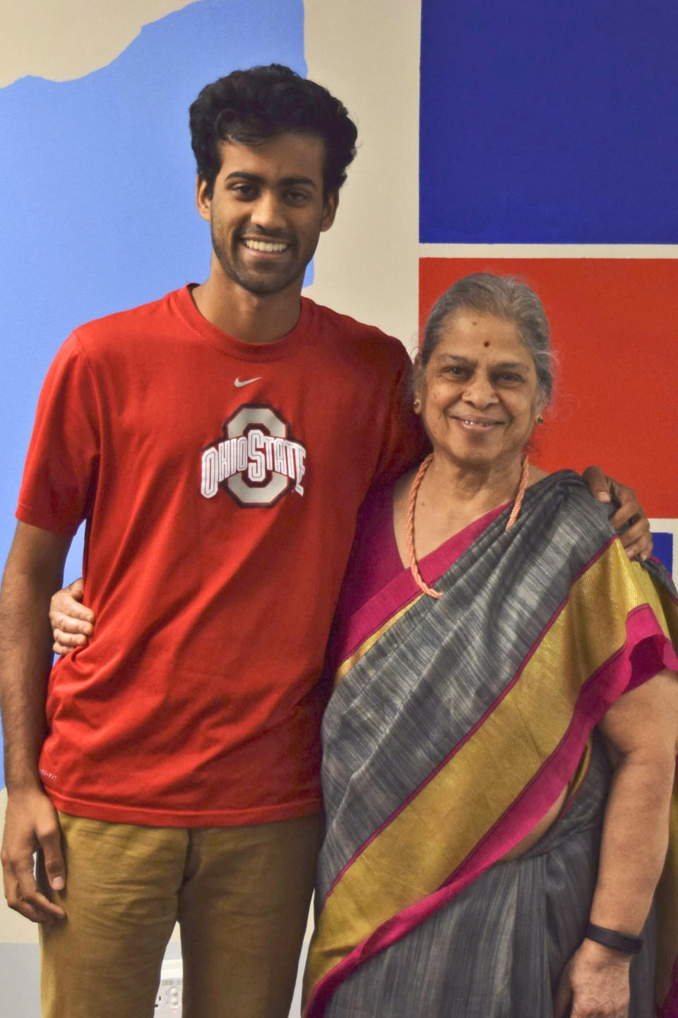 In this photo provided by courtesy of Arman Ramnath, Ramnath poses with his grandmother, Saroja Seetharaman, Oct. 5, 2016, in Columbus, Ohio. In Ramnath's family, his India-born maternal grandmother, Seetharaman, rotates among her three children and their six grandchildren, in Dallas, Atlanta and his Columbus home. The pandemic and its isolating restrictions have been especially tough for many of the nation's some 70 million grandparents, many at ages when they are considered most vulnerable to the deadly COVID-19 virus. (Arman Ramnath via AP)