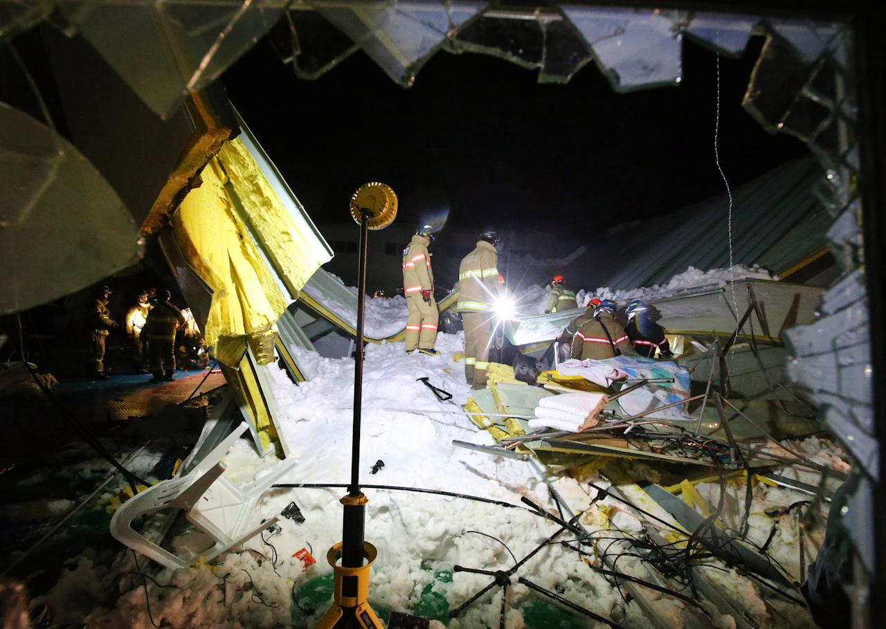 Rescue workers search for survivors from a collapsed resort building in Gyeongju, South Korea, Monday, Feb. 17, 2014. Four university students died and about 10 were feared trapped after the roof of a building collapsed in a southeastern city during a welcoming ceremony for freshmen, South Korean officials said Tuesday. (AP Photo/Yonhap, Lee Jae-hyuck) Korea Out