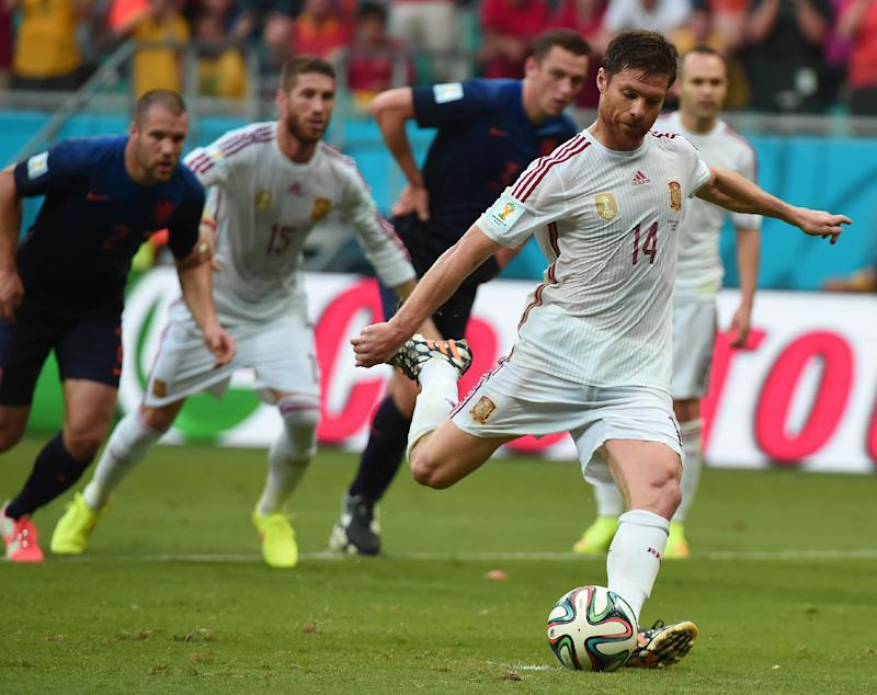 Spain's midfielder Xabi Alonso (front) scores a penalty during a football match between Spain and the Netherlands in Salvador during the 2014 FIFA World Cup on June 13, 2014