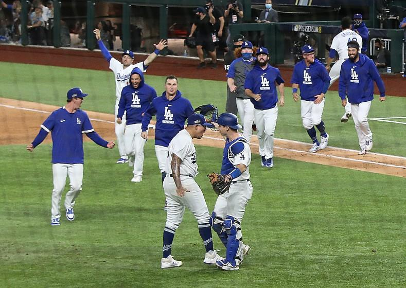 Julio Urías is greeted by catcher Will Smith as Dodgers teammates rush on the field after a Game 7 win over Atlanta.