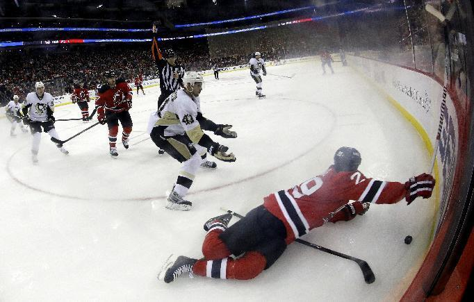 In this photograph taken with a fisheye lens, New Jersey Devils left wing Ryane Clowe, right, hits the ice after being fouled by Pittsburgh Penguins defenseman Robert Bortuzzo, left, during the second period of an NHL hockey game, Tuesday, Dec. 31, 2013, in Newark, N.J. Bortuzzo was sent to the penalty box after the play. (AP Photo/Julio Cortez)