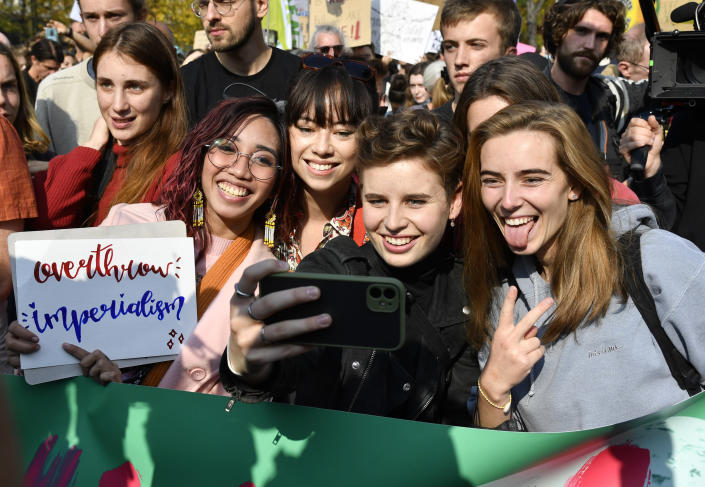 Belgian climate activist Anuna De Wever, center, takes a selfie as she poses with participates in a climate march in Brussels, Sunday, Oct. 10, 2021. Some 80 organizations are joining in a climate march through Brussels to demand change and push politicians to effective action in Glasgow later this month.(AP Photo/Geert Vanden Wijngaert)