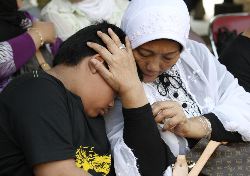 An Indonesian woman comforts his grandson whose father was on board of the Russian-made plane that crashed into a mountain in West Java, as they wait for the identification process of the victims at the main police hospital in Jakarta, Indonesia, Saturday, May 12, 2012. Search teams were struggling to retrieve the bodies of the 45 people who were aboard the Sukhoi Superjet-100 that crashed on Wednesday during a demonstration flight for potential buyers. (AP Photo/Dita Alangkara)