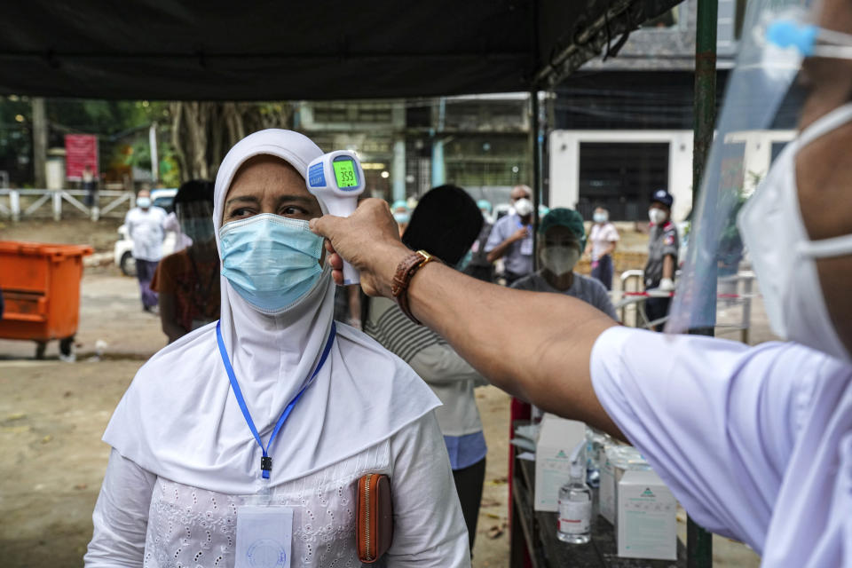 A woman gets her temperature checked before entering a polling station Sunday, Nov. 8, 2020, in Yangon, Myanmar. Voting was underway in Myanmar's elections on Sunday, with the party of Nobel Peace Prize laureate Aung San Suu Kyi heavily favored to retain power it had wrestled from the powerful military five years ago. (AP Photo/Aung Naing Soe)