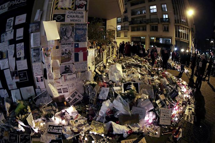 """People visit a makeshift memorial near the headquarters of the French satirical weekly Charlie Hebdo at the end of the unity rally """"Marche Republicaine"""" on January 11, 2015 in Paris (AFP Photo/Joel Saget)"""