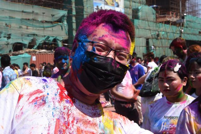 A tourist wearing a facemask amid fears of the spread of COVID-19 novel coronavirus, poses as he celebrates Holi, the spring festival of colours, on March 9, 2020. - Holi is observed at the end of the winter season on the last full moon of the lunar month. (Photo by PRAKASH MATHEMA / AFP) (Photo by PRAKASH MATHEMA/AFP via Getty Images)
