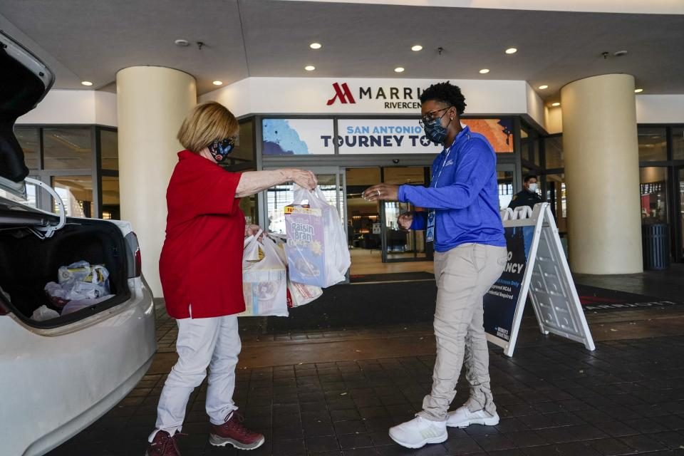Volunteer Joan Kearl hands food to Amber Wilson outside a hotel Friday, March 26, 2021, in San Antonio. Kearl picked up the food for the quarantined Louisville women's basketball team participating in the NCAA tournament. The NCAA and local organizing groups set up expanded ambassador and item-delivery services relying on volunteer help to take care of needs for players, officials and others working inside. (AP Photo/Morry Gash)