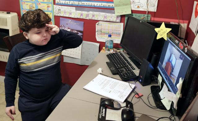 In this Tuesday, Jan. 22, 2013 photo, Devon Carrow stands for the Pledge of Allegiance while attending school from home while operating a robot in the classroom, in Orchard Park N.Y. Carrow's life-threatening allergies don't allow him to go to school. But the 4-foot-tall robot with a wireless video hookup gives him the school experience remotely, allowing him to participate in class, stroll through the hallways, hang out at recess and even take to the auditorium stage when there's a show. (AP Photo/David Duprey)