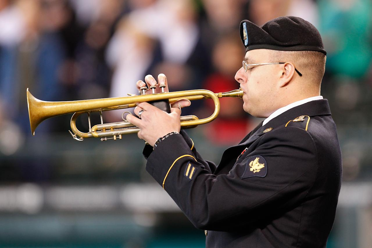 "SEATTLE, WA - MAY 27:  A member of the military plays ""Taps"" as part of Memorial Day ceremonies prior to the game between the Seattle Mariners and the San Diego Padres at Safeco Field on May 27, 2013 in Seattle, Washington.  (Photo by Otto Greule Jr/Getty Images)"