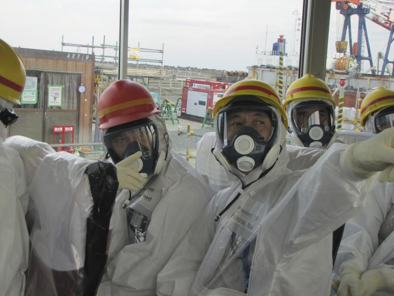 Handout photo showing Moniz and Hirose wearing protective suits and masks as they inspect TEPCO's Fukushima Daiichi nuclear power plant