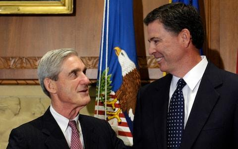 James Comey talks with outgoing FBI Director Robert Mueller in 2014 - Credit: AP