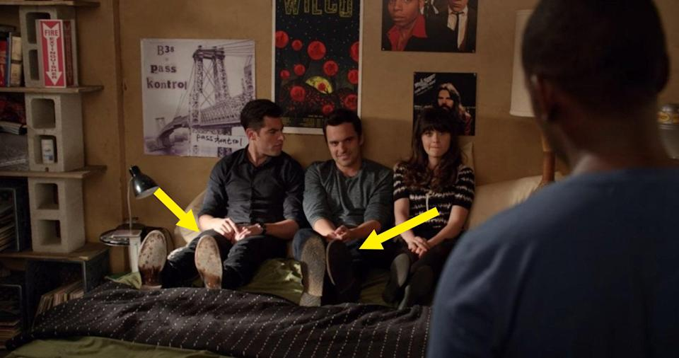 Schmidt, Nick, and Jess sitting on a bed while wearing their shoes
