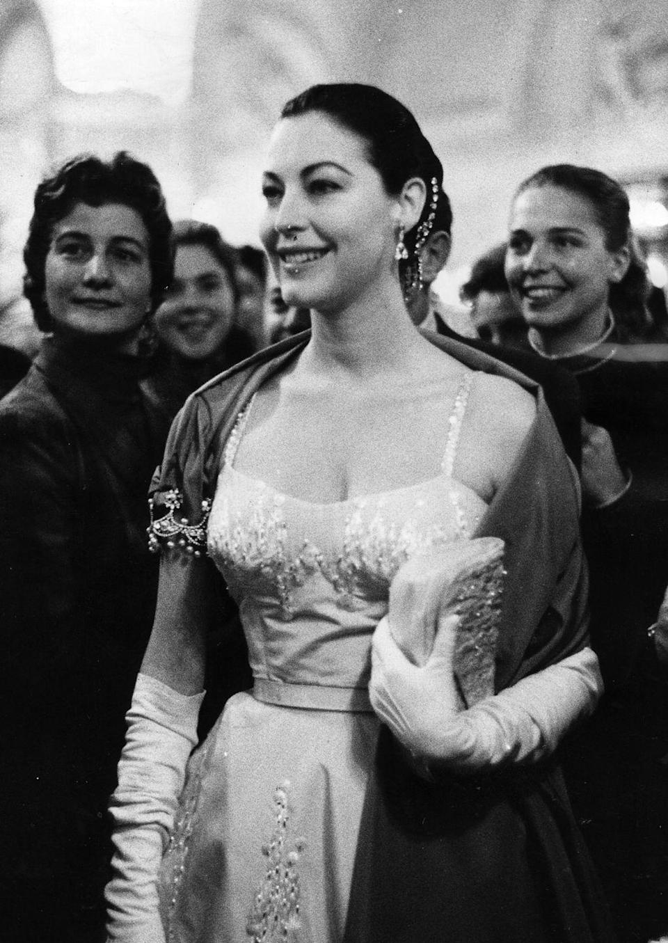 <p>Here, Gardner wears an embroidered and bejeweled dress and wrap while attending the wedding of her good friend Grace Kelly to Prince Rainier of Monaco. </p>