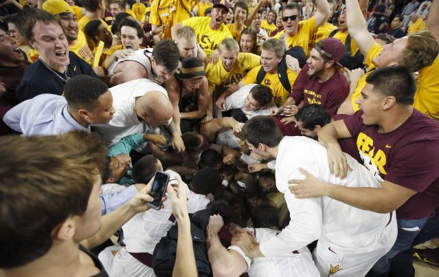 Arizona State layers and fans celebrate on the court after an NCAA college basketball game win against Arizona, Friday, Feb. 14, 2014, in Tempe, Ariz. Arizona State defeated Arizona 69-66 in double overtime. (AP Photo/Ross D. Franklin)