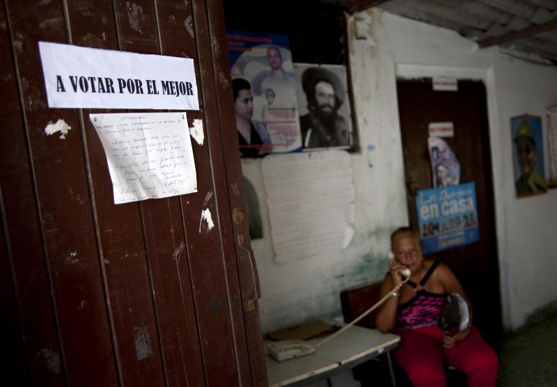 "A woman answers the phone at a boxing gym where a sign hangs on the door that reads in Spanish ""A vote for the best"" ahead of municipal assembly elections in Old Havana, Cuba, Saturday, Oct. 20, 2012. On Sunday, Cubans will cast ballots to choose among candidates for municipal assemblies that administer local governments and relay complaints on issues such as potholes and housing, social and sports programs. (AP Photo/Ramon Espinosa)"